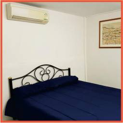 white painted room with doube bed and aircon unit