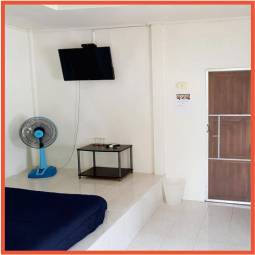 white painted room with doube bed, television and floor fan
