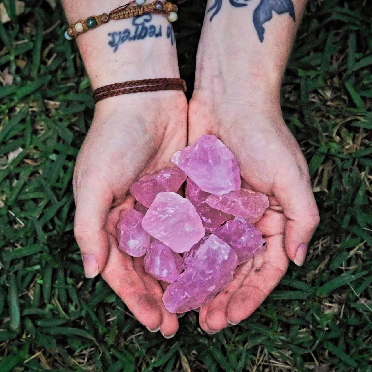 hands holding pink, rose quartz crystals
