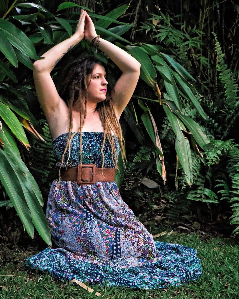 Girl in garden, yoga pose, with dreadlocks